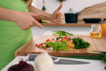 Close up of  woman's hands cooking in the kitchen. Housewife offering ​​fresh salad with thumbs up. Vegetarian and healthily cooking concept