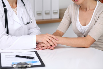 Close up of a doctor reassuring her female patient while  sitting at the desk. Medicine, help and health care concept