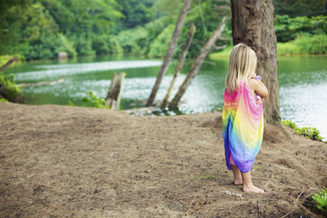 A young girl stands on the beach at the water's edge; Kauai, Hawaii, United States of America
