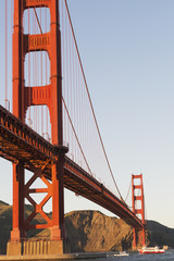 Tour boats cross under Golden Gate Bridge, viewed from Fort Point at the entrance to San Francisco Bay, Marin Headlands visible in background; San Francisco, California, United States of America