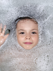 Face of a young boy surrounded by bubbles in the bathtub; Montreal, Quebec, Canada