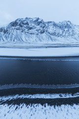 Snow Covered Landscape Along The Eastern Shore Of Iceland As A Stream Flows Gently Past With Ice Forming Along The Shore Of It; Iceland