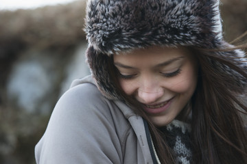 Portrait Of A Young Woman Wearing A Fur Trimmed Hat And Looking Down; Iceland