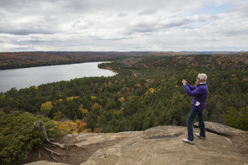 Woman takes pictures of Rock Lake from atop Booth's Rock, Algonquin Park; Ontario, Canada