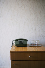 Hotel nightstand with push-button phone and water glasses, textured wallpaper; Kiev, Ukraine
