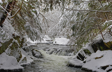 Water flowing in a river with snow covered shoreline; Fulford, Quebec, Canada