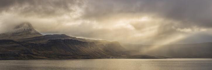 Clouds with sunbeams over bay, Djupavik, Iceland