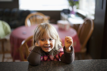 Young girl sitting at the kitchen counter; Surrey, British Columbia, Canada