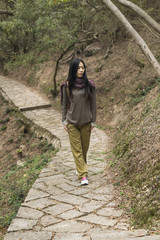 Young woman walking on a trail; Xiamen, China