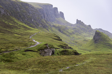 Fog covers the green landscape with cliffs and peaks; Scotland