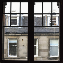 View out a window to a residential building where the lines of the architectural detail are blurred; Edinburgh, Scotland
