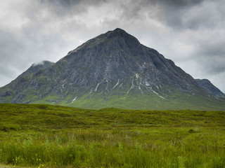 Rugged peaked mountain under a cloudy sky with lush grass in a field; Scotland