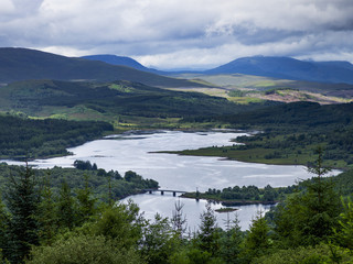 Landscape of a river and forests over mountains under a cloudy sky; Scotland
