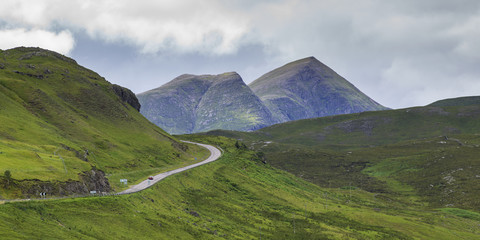 A road winding through the mountains with two mountain peaks under a cloudy sky in the Highlands; Scotland