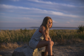 Girl in contemplation sitting on a rock on the beach at sunset; Surrey, British Columbia, Canada