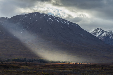 Shaft of light lights up colorful tundra along the Haines Highway near Mule Creek, Alsek-Tatshenshini Wilderness, British Columbia, Canada