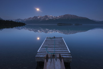 Boat dock with a full moon rising over the Chigmit Mountains at Lake Clark in Lake Clark National Park and Preserve, Alaska.