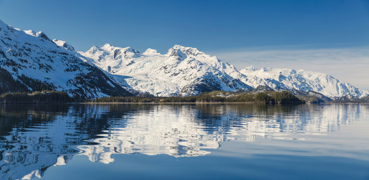 Snow covered mountains reflected in water, Kings Bay, Prince William Sound, Whittier, Alaska, USA