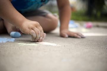 Child playing with sidewalk chalk; Regina, Saskatchewan, Canada