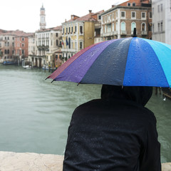 Person holding wet colorful umbrella while looking at canal