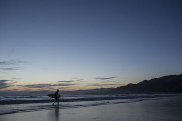 Man walking on beach with surf board; San Luis Obispo, California, United States of America