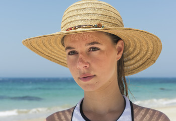 Portrait of a young woman on the beach wearing a sunhat; Tarifa, Cadiz, Andalusia, Spain