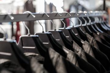 Black clothes on a black hangers