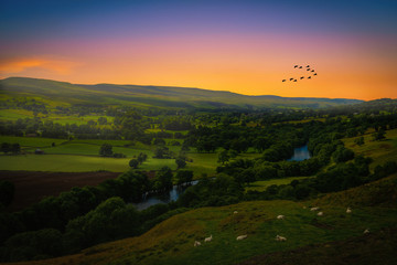 Sunset over mountains and meandering River making its way through lush green rural farmland in England. Wall mural