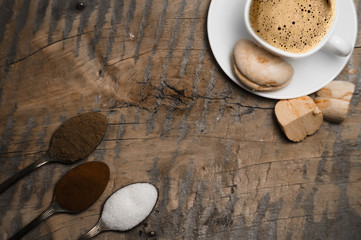Coffee with foam and brown marshmallow on a wooden table