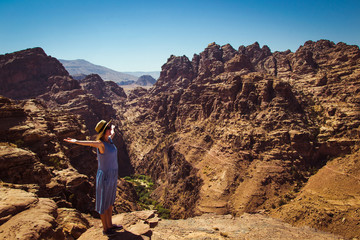 Freedom traveler woman standing with raised arms enjoying amazing mountain landscape. View from Petra to Wadi Araba desert. Hipster young girl love travel, freedom. Summer vacation. Copy space
