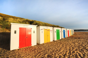 row of wooden painted brightly coloured beach huts