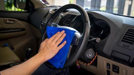 A man cleaning a steering wheel, clean a car interior