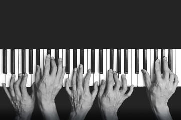 five hands playing on piano keys, black and white. music background