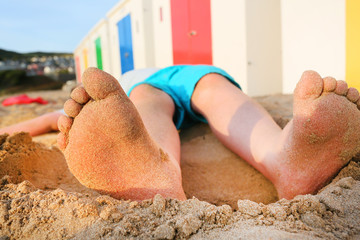 sandy feet of a young boy lying on a beach