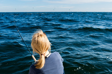 Woman fishing on sea, back of head