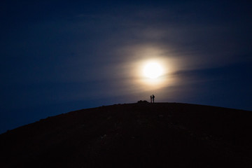 Silhouetted couple standing on hilltop in full moon night