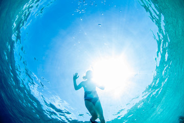 Woman floating on sea surface, low angle view, Staniel Cay, Bahamas, Caribbean