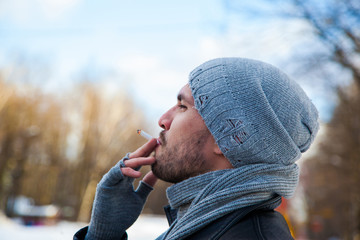 Handsome man is smoking outdoor in winter. Blurred background.