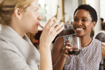 Female friends sharing wine at dinner party