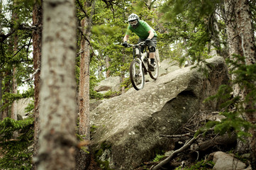 Mountain biker jumping in forest