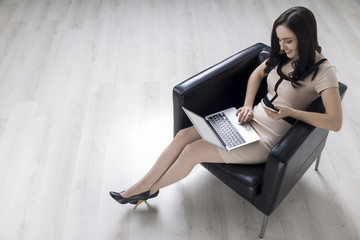Woman in an armchair with a laptop