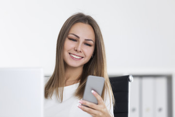 Smiling girl looks at a screen of smartphone