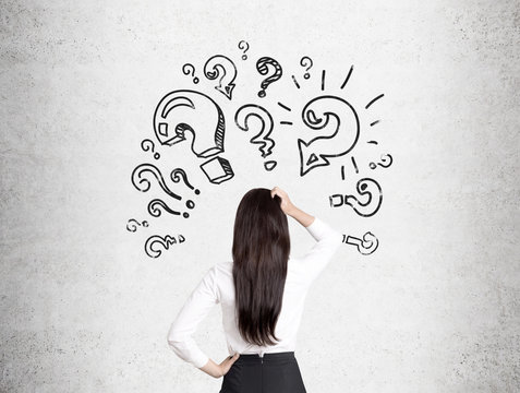Woman scratches head and looks at question marks