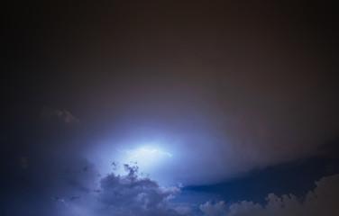 Lightning strike on the cloudy dark sky. Fantastic summer night