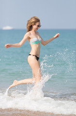 Girl in swimwear and sunglasses running along seashore arms outstretched