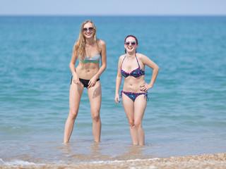 Two girls in bikini standing in sea water laughing