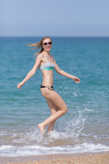 Young woman in bikini and sunglasses running along seashore