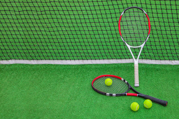 tennis racket with balls on green grass