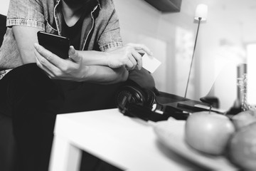 young man is sitting on sofa shopping on line with smart phone listening music with headphones is holding credit card on his hand in living room,omni channel concept,black and white