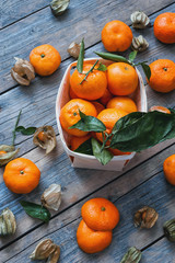 the fruits of fezalis and orange tangerines with leaves and twigs, lie on wooden old table